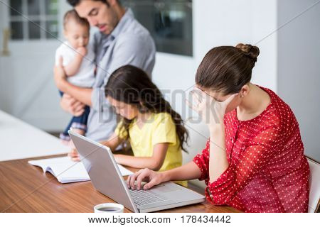 Tensed mother working on laptop with father helping daughter in homework at home