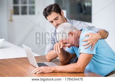 Son comforting tensed father sitting at desk with laptop