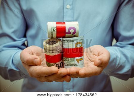 A man holding a bundle of American currency in his hands