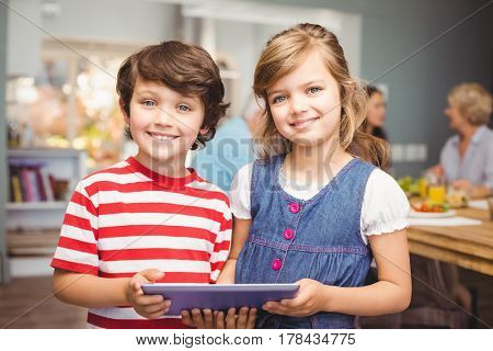 Portrait of brother and sister using digital tablet at home