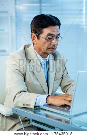 Focused businessman using laptop in office