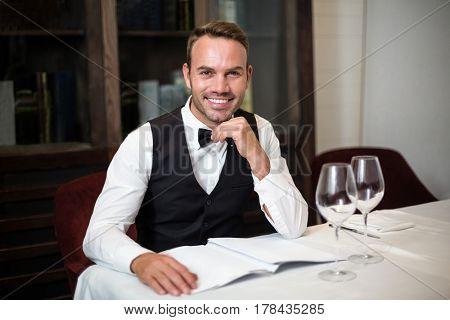 Portrait of waiter reading the menu in a fancy restaurant