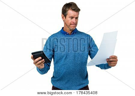 Shocked man holding calculator and paper against white background
