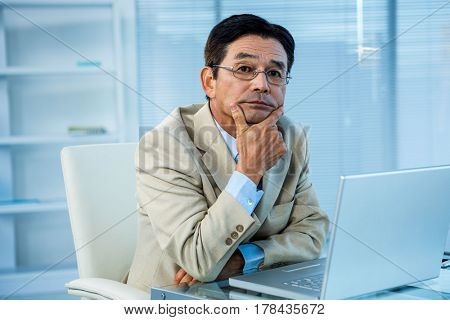 Thoughtful asian businessman looking at the camera in office