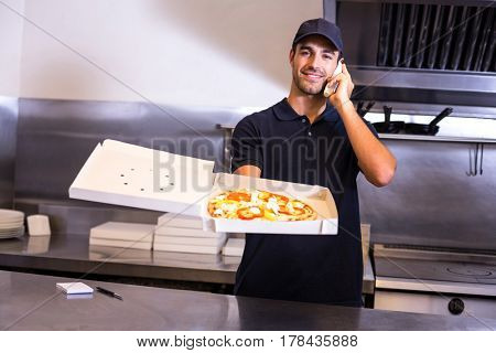 Pizza delivery man taking an order over the phone in a commercial kitchen