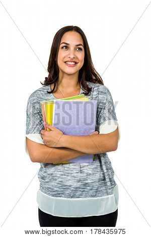 Close-up of smiling woman holding books against white background