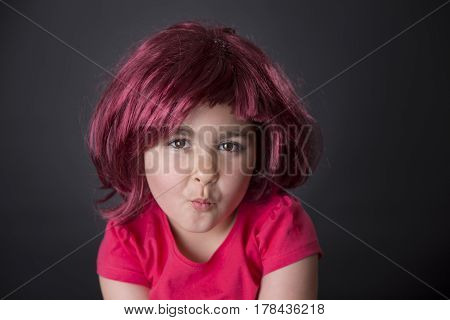 Portrait of a funny five years girl with pink wig pouting on black background. Studio shot