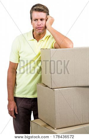 Sad man standing by with boxes against white background