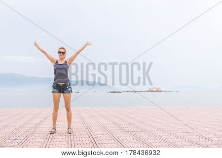 The young girl raised her arms up to the sun on a background of mountains, sea and sky with clouds