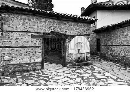 Bansko, Bulgaria - March 20, 2017: Old house stone paved road alley, wooden benches Bansko ski tourist centre of Bulgaria