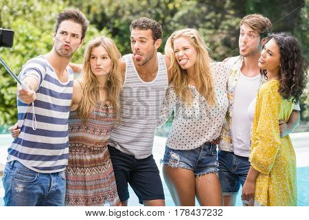 Group of friends making funny faces while taking a selfie near pool