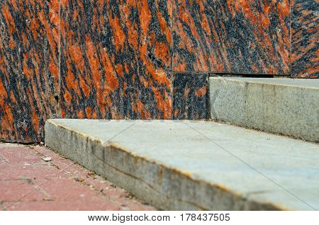 Granite wall texture as background against natural stone stair element
