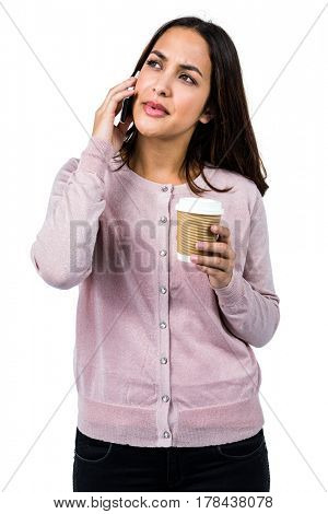 Woman talking on phone while holding coffee against white background