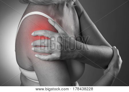 Pain in shoulder care of female hands ache in woman's body black and white photo with red spots