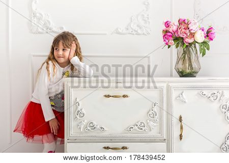 The little girl in a red skirt leaned on the dresser. On the dresser is a bouquet of tulips.