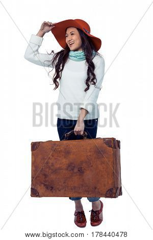 Smiling Asian woman holding luggage holding hat on white screen
