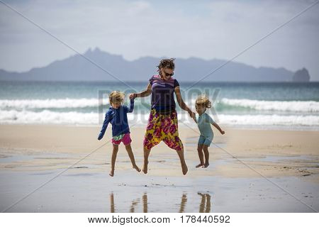 Happy woman and children on beach