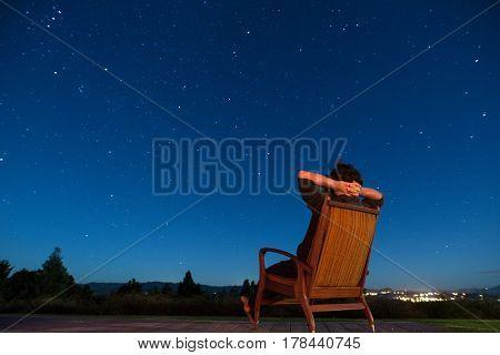 Man sitting in armchair under the stars