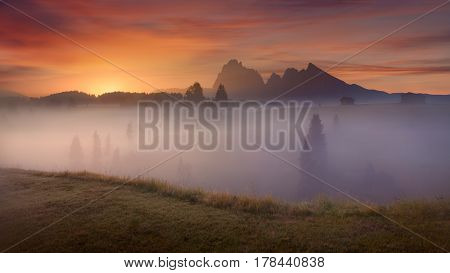 Misty landscape view in Alpe di Siusi or Seiser Alm at beautiful dawn. Long exposure photo - Dolomites mountain range Italy.