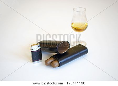 Glass of whiskey and two cigars leather black cigar lighter isolated on a white background