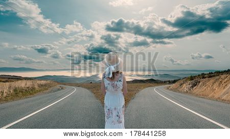 Woman standing in front of two roads and deciding for best solution for her life travel. Success concept.
