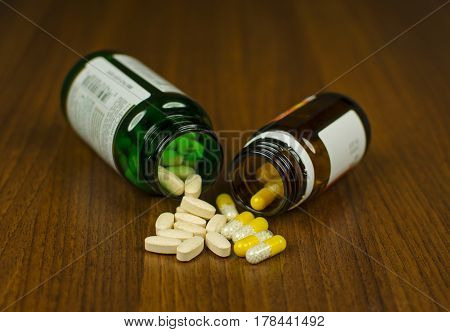 View of two glass with pills lying side by side on a wooden background