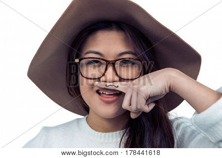 Asian woman with mustache on finger posing for the camera on white screen