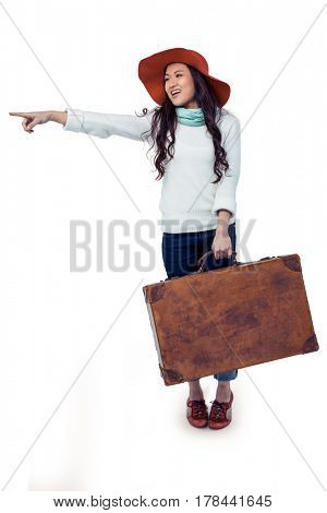 Smiling Asian woman holding luggage pointing somewhere on white screen