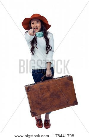 Smiling Asian woman holding luggage pointing the camera on white screen