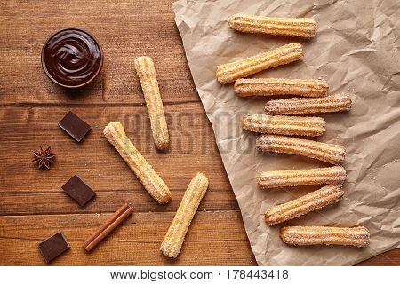 Churros traditional Spain culture breakfast or lunch sweet dough dessert pastry street fast food snack with chocolate on rustic wooden table background. Flat lay top view