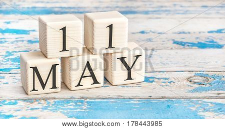 May 11th. Wooden cubes with date of 11 May on old blue wooden background.