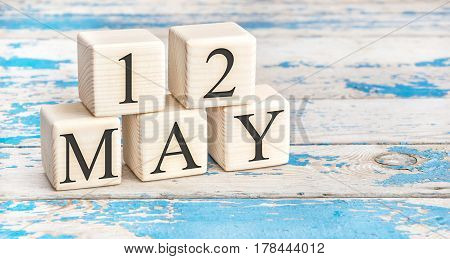May 12th. Wooden cubes with date of 12 May on old blue wooden background.