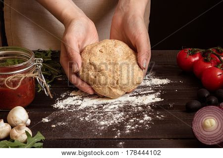 Woman Preparing Dough For Pizza. Hands Holding Dough On The Wooden Table
