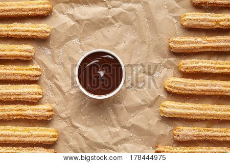 Churros traditional homemade Spain breakfast or lunch street fast food baked sweet dough snack dessert with chocolate dipping on rustic decorative parchment paper background. Flat lay top view