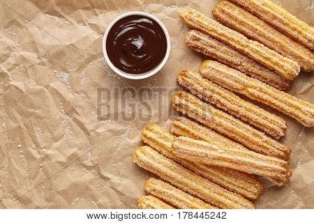 Churros traditional homemade Spain breakfast or lunch meal street fast food baked sweet dough snack dessert with chocolate dipping on rustic decorative parchment paper background. Flat lay top view