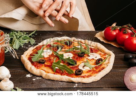 Hands Cooking Pizza In The Kitchen. Pizza Ingredients On The Wooden Table