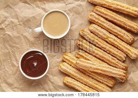 Churros traditional homemade Spain breakfast meal street food baked sweet dough dessert with cup of coffee and chocolate dipping on rustic decorative parchment paper background. Flat lay top view