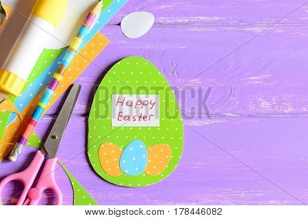 Happy Easter greeting card, craft tools and materials on purple wooden background with copy space for text. Cute greeting card made in form of egg with wishes Happy Easter. Bright Easter background