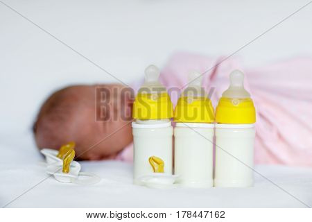 Cute newborn baby girl with nursing bottles and pacifier. Formula drink for babies. New born child, little girl laying in bed. Family, new life, childhood, beginning, bottle-feeding concept.