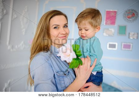 The young woman holds on hands of the little son. She looks in the camera and smiles. In hands at the kid a flower.