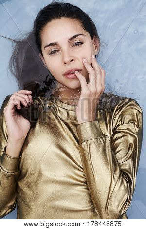 Portrait of sensuous woman wearing gold in water