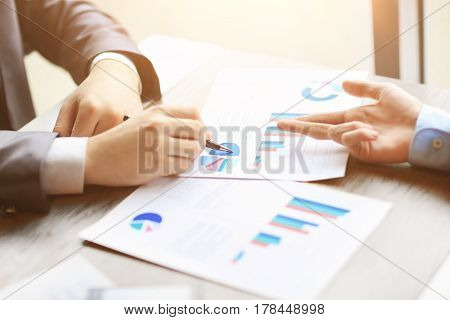 Image of human hands with pens pointing at business document at meeting