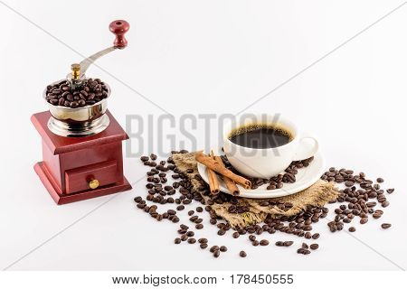 Coffee grinder winch and Coffee cup with beans on hemp sack decorated with cinnamon sticks isolated on white background