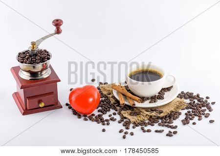 Coffee grinder winch Red heart icon and Coffee cup with beans on hemp sack decorated with cinnamon sticks isolated on white background
