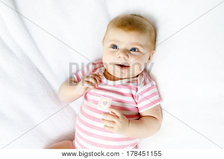 Cute adorable newborn baby in white bed on a blanket. New born child, little adorable girl looking surprised at the camera. Family, new life, childhood, beginning concept.