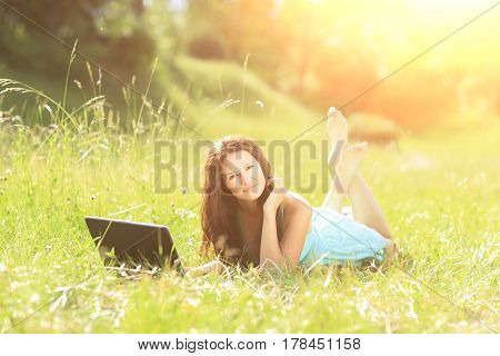 Beauty girl with laptop outdoors in a park on a sunny day