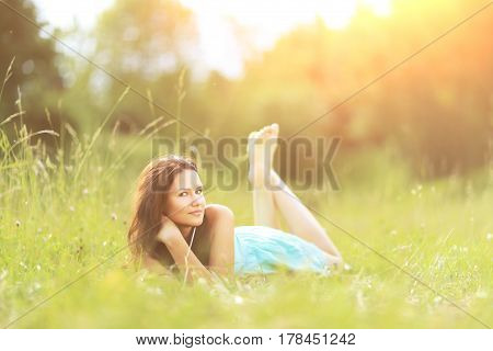 Beautiful young woman on grass in summer park on sunny day