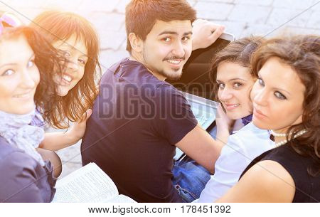 Group of cheerful students with a laptop on a college background on a sunny day