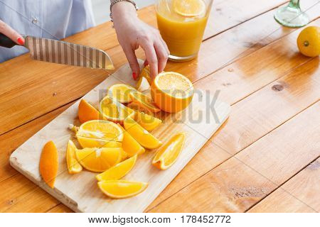 Mom cuts fruit to her son. sliced oranges on a wooden cutting board. Healthy and tasty breakfast.
