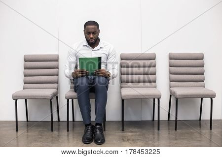 Time for job interview. Young handsome Afro-American man in office. Man sitting, holding his CV and waiting for job interview. Empty chairs are near man. Nice light interior